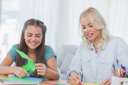 Mother and daughter doing arts and crafts together at home in living room
